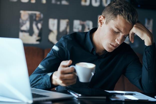 テーブルマネージャーのカフェでノートパソコンを持つビジネス男フリーランサーは、一杯のコーヒーモデルを文書化します。