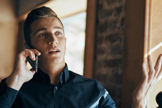 カフェラップトップ通信電話ルームマネージャーモデルで働くビジネス男フリーランサー。高品質の写真