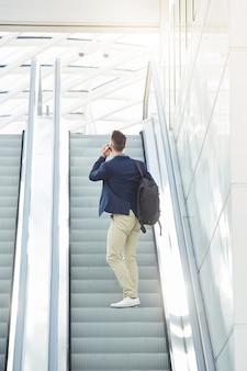 Деловой человек из-за стояния на эскалаторе по телефону