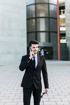 Business man in front of the office building using his mobile phone