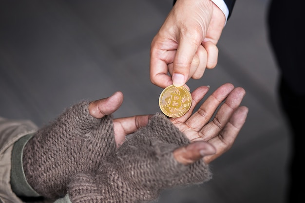 Business man give his gold bitcoin to homeless man