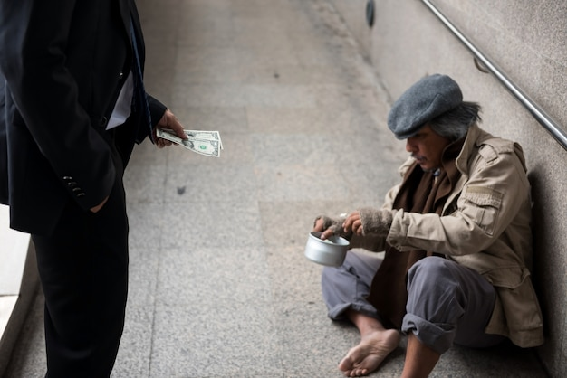 Business man give money to homeless man