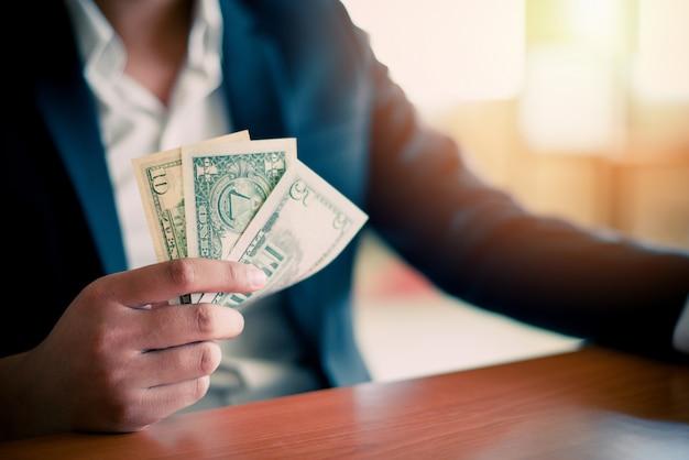 紙幣を与え、お金の現金を手に保持しているビジネスマン-ビジネスマンの紙幣クレジットの成功の概念が豊富