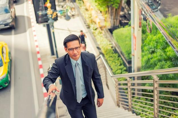 ビジネスの男性がhに働くためにラッシュアワーで階段を上る