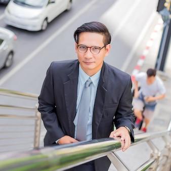 ビジネスの男性が仕事にラッシュアワーで階段を上る。急いでください。