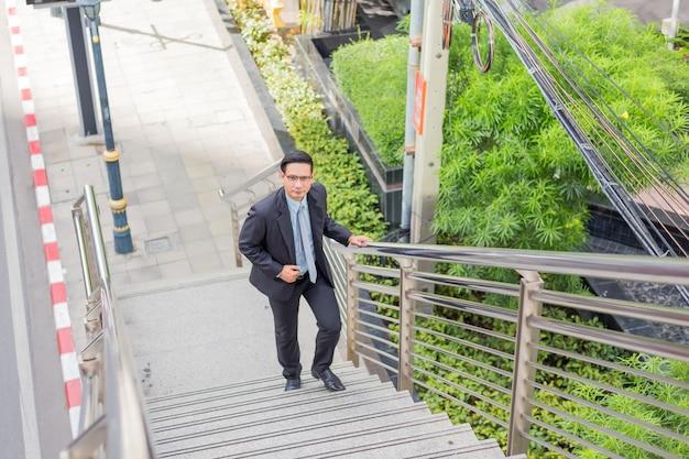 ビジネスの男性が仕事にラッシュアワーで階段を上る。
