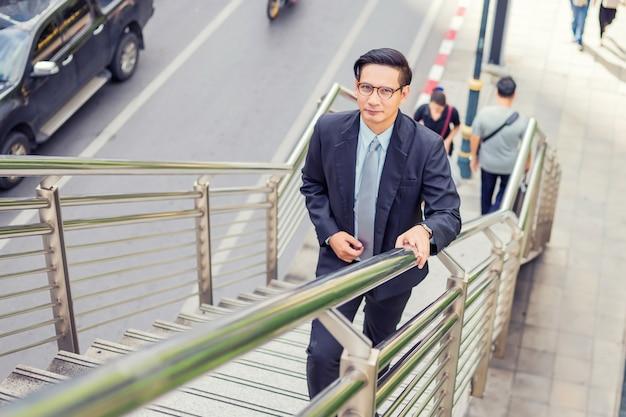 ビジネスマンは仕事にラッシュアワーで階段を上る。