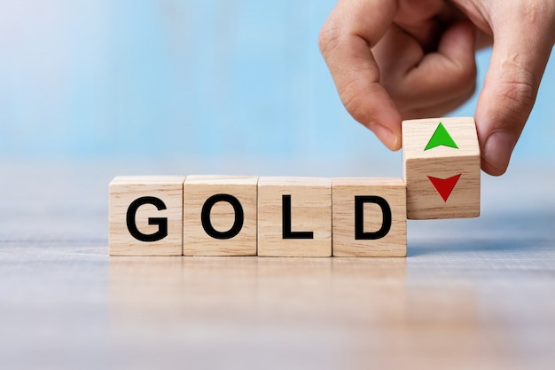 ビジネスの男の手は、ゴールドのテキストが付いたウッドキューブブロックを上下の矢印記号に変更します。