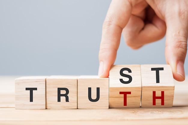 비즈니스 맨 손은 테이블 배경에 trust 및 truth 비즈니스 단어로 나무 큐브 블록을 변경합니다. 신뢰할 수 있는 믿음, 믿음 및 정직 개념