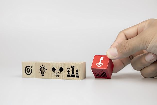 ビジネスの男の手は、ビジネス戦略アイコンのキーを持つキューブ木製おもちゃのブログを選択します。