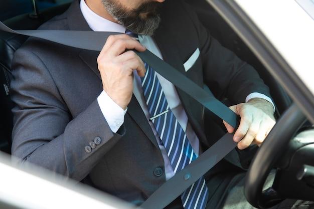 Ремень безопасности пристегивания руки бизнесмена в машине. концепция безопасности прежде всего.