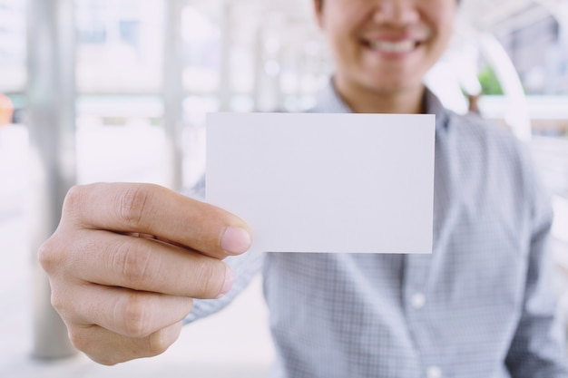 Business man in hand hold show blank white card mock up with rounded corners.