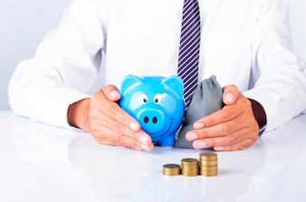 Business man hand holding blue piggy bank and money bag