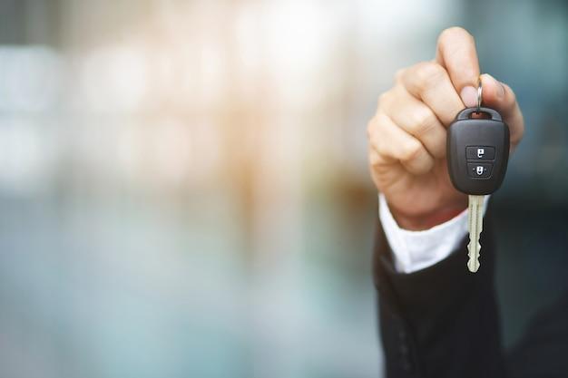 車のキーを持っているビジネスマンの手。輸送ディーラーと販売コンセプト