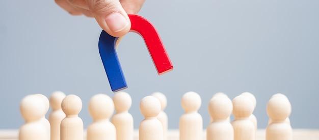 Деловой человек рука магнит и вытаскивая деревянную фигуру человека из толпы сотрудника. бизнес, управление человеческими ресурсами, подбор персонала, работа в команде, стратегия, токсичные люди и концепции лидерства