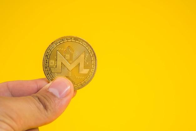 비즈니스 남자 손을 노란색 표면에 손가락 사이 monerd 동전을 들고.
