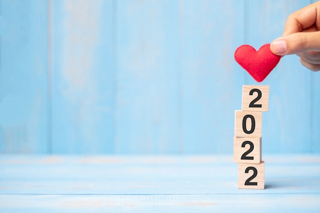 Business man hand holding red heart shape over 2022 wooden cubes on blue table background with copy space for text. business, resolution, new year new you and happy valentine's day holiday concept