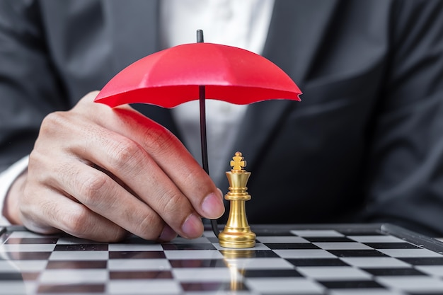 Business man hand holding red umbrella cover chess king figure.