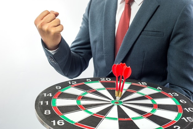 Business man hand holding a target with darts hitting the center over white background.