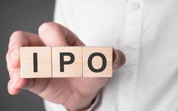 Ipo 텍스트와 함께 나무 큐브를 들고 사업가 손. 금융, 마케팅 및 비즈니스 개념