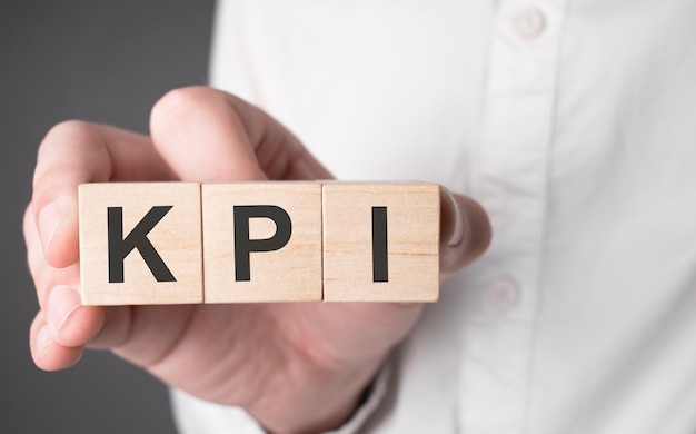 Kpi 텍스트가 있는 나무 큐브를 들고 있는 사업가의 손. 금융, 마케팅 및 비즈니스 개념