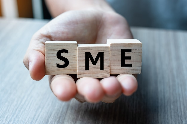 Business man hand holding wooden cube with sme text