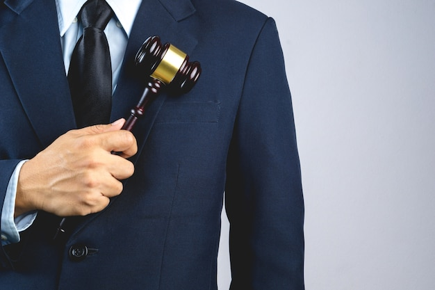 Business man hand holding wooden judge's gavel as a law or justice sign