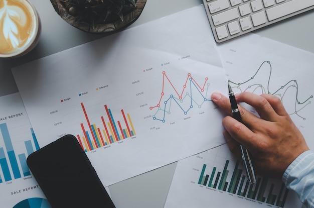 Рука делового человека держит ручку на деловых документах, графиках, отчетах и инвестициях. на сером столе, мобильном телефоне, кофе и клавиатуре компьютера. вид сверху
