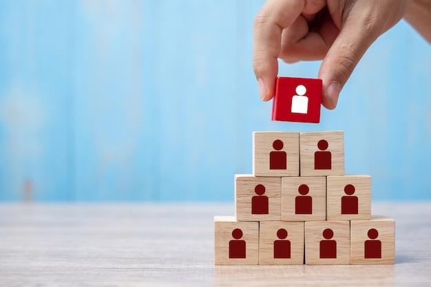 ビジネスの男の手の配置または人と赤い木製ブロックを引っ張る