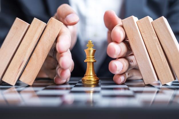 Рука бизнесмена защищает фигуру шахматного короля и останавливает падающие деревянные блоки или домино.