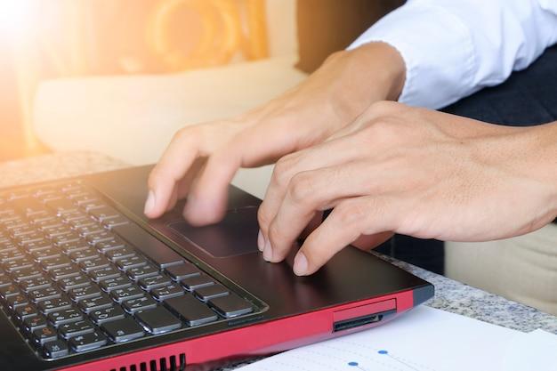Деловой человек рука набрав на портативный компьютер