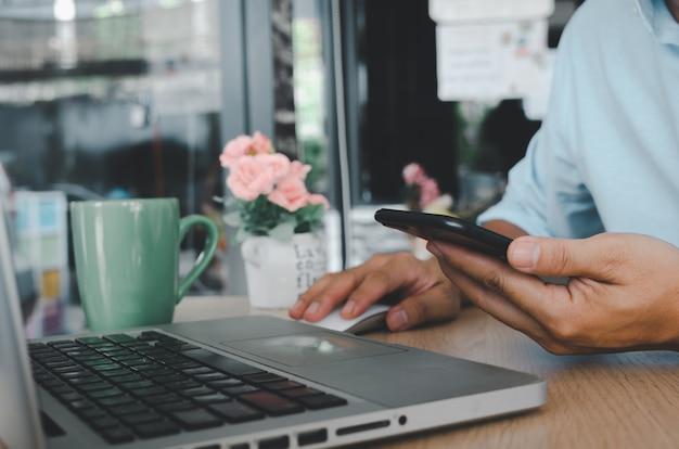 Деловой человек рука с помощью мобильного смартфона и мыши компьютерный ноутбук на table.searching интернет-технологии. социальные медиа онлайн бизнес-концепция