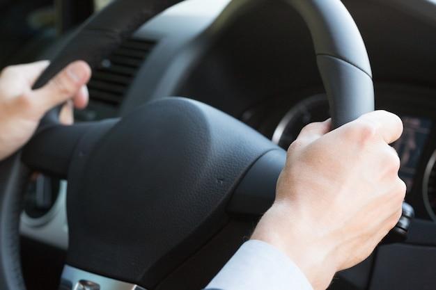 Business man hands on steering wheel luxury car