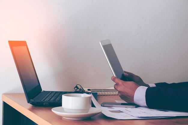 Business man hands on a table with tablet, phone and cup of coffee in a office