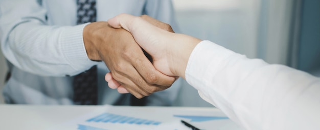 Business man handshake deal with partner after finishing up business meeting in meeting room office