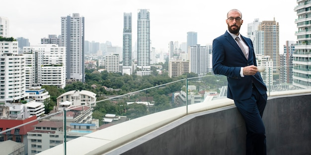 Business man having a coffee break in a balcony with a cityscape background