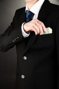 黒のポケットにお金を隠すビジネスマン