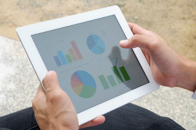 Business man hold analyzing financial chart on tablet , strategy concept , business idea , business concept