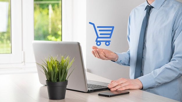 Business man hold in hand shopping cart icon.shopping online concept.basket hologram. online shopping, online store application in a smartphone. digital marketing online