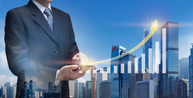 Business man hold mobile present chart up of business success plan, financial, profit growth, stock. businessman use smart phone show arrow graph up of building, office tower, property, real estate.