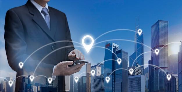 Деловой человек удерживает смартфон, находит местоположение в городе с помощью карты gps-навигатора. бизнесмен в городе использует интернет-сеть gps на мобильном телефоне 5g показывает значок местоположения gps, бизнес-здание, путешествия, концепцию 5g.