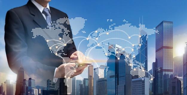 Деловой человек держит смарт-телефон, выставочное офисное здание, современную башню, собственность, недвижимость, бизнес-инвестиционную концепцию. бизнесмен использует интернет-сеть 5g на мобильном телефоне, чтобы найти местоположение gps на карте мира