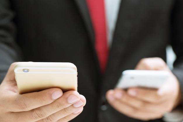 ビジネスマンは携帯電話の転送データ情報を使用して両手を握ります。