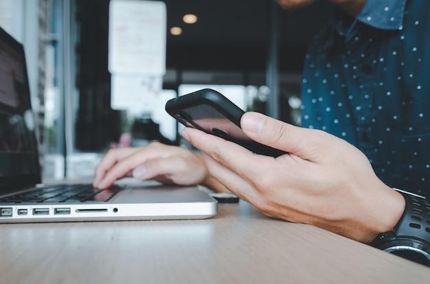 Деловой человек, держащий сотовый телефон, глядя на рабочие данные и портативные компьютеры на столе в офисе. концепция бизнеса и технологий