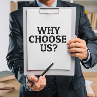 クリップボードを持っているビジネスマンがなぜ私たちを選ぶのか質問