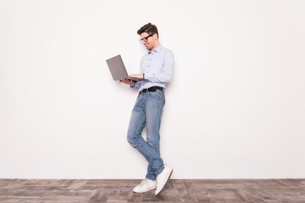 ホワイトスペースで分離されたラップトップを保持しているビジネスの男性