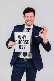 Деловой человек, держащий бумагу с вопросом, почему выбирают нас