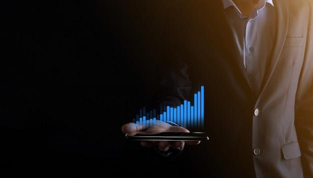 홀로그램 그래프와 주식 시장 통계를 들고 보여주는 비즈니스 남자는 이익을 얻습니다. 성장 계획 및 비즈니스 전략의 개념 좋은 경제 형태의 디지털 화면 표시