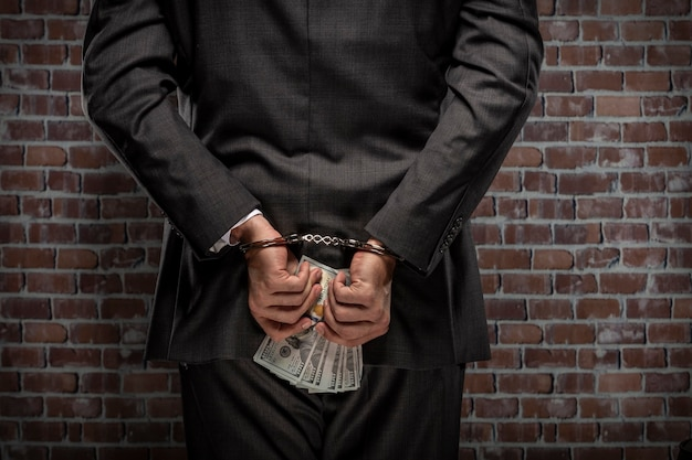 Business man holding bills of money with a handcuff in a jail. concept of corruption, corrupt politicians, illegal businesses. brick background.