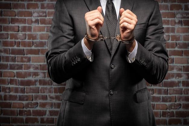 刑務所で手錠で紙幣を保持しているビジネスの男性。腐敗、腐敗した政治家、違法ビジネスの概念。レンガの背景。